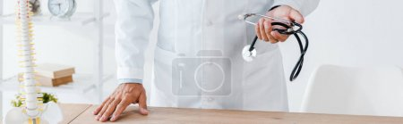 Photo for Panoramic shot of doctor holding stethoscope near table in clinic - Royalty Free Image