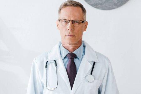 Photo pour Beau médecin en lunettes et manteau blanc regardant la caméra - image libre de droit