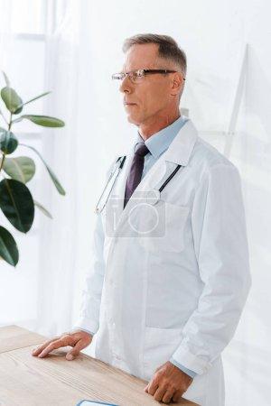 Photo pour Beau médecin en manteau blanc et des lunettes debout près du bureau - image libre de droit