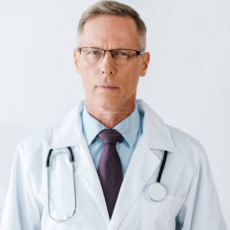 Photo for Serious doctor in glasses and white coat looking at camera - Royalty Free Image