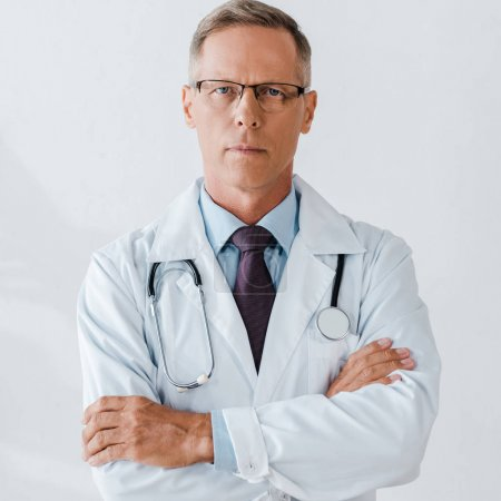 Photo for Handsome doctor with stethoscope standing with crossed arms and looking at camera - Royalty Free Image