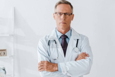 Photo for Doctor with stethoscope standing with crossed arms and looking at camera - Royalty Free Image