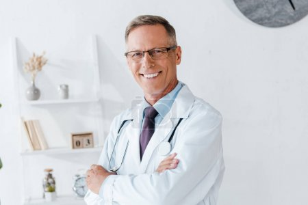 Photo for Happy doctor in white coat and glasses with crossed arms - Royalty Free Image