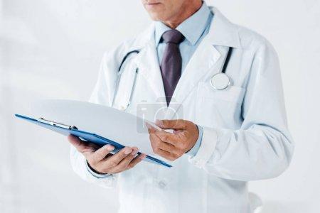 Photo pour Vue recadrée du médecin en manteau blanc tenant la page et presse-papiers dans la clinique - image libre de droit