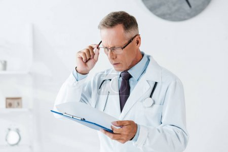 Photo for Handsome man in white coat touching glasses while looking at clipboard in clinic - Royalty Free Image