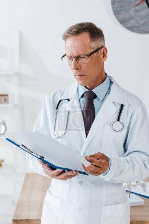 Foto de Guapo médico en capa blanca mirando el portapapeles en el hospital - Imagen libre de derechos