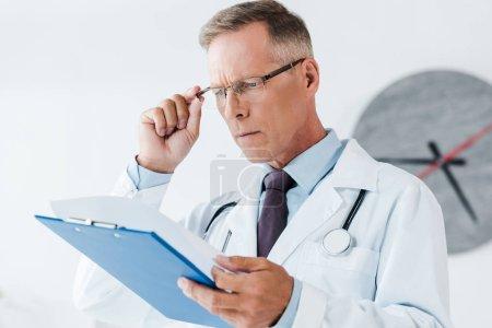 Photo pour Foyer sélectif du beau docteur dans le manteau blanc regardant le presse-papiers et touchant des verres dans l'hôpital - image libre de droit