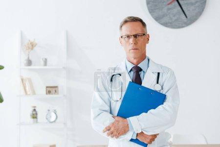 Photo pour Médecin sérieux dans les lunettes debout et tenant le presse-papiers tout en regardant l'appareil photo - image libre de droit