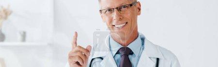 Panoramaaufnahme eines glücklichen Mannes mit Brille, der mit dem Finger in die Klinik zeigt