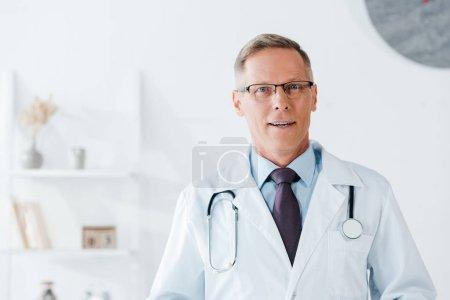 Photo pour Beau médecin en lunettes regardant la caméra à l'hôpital - image libre de droit