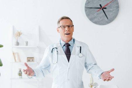 Photo pour Médecin surpris en manteau blanc et lunettes geste à la clinique - image libre de droit