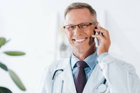 Photo for Happy doctor looking at camera and talking on smartphone in clinic - Royalty Free Image