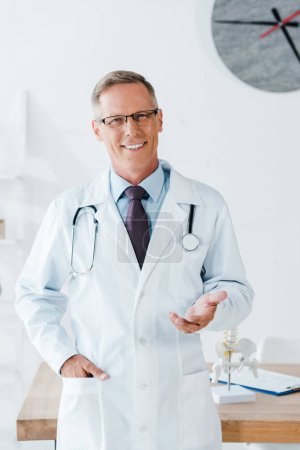 Photo for Happy doctor in glasses gesturing while standing with hand in pocket - Royalty Free Image