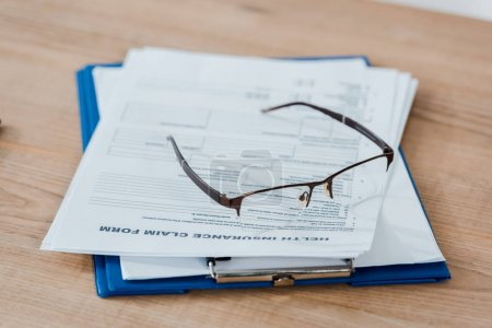 Photo pour Mise au point sélective des lunettes sur le presse-papiers avec des documents - image libre de droit