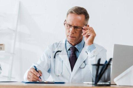 Photo pour Mise au point sélective de beau médecin touchant des lunettes tout en écrivant sur le presse-papiers à l'hôpital - image libre de droit