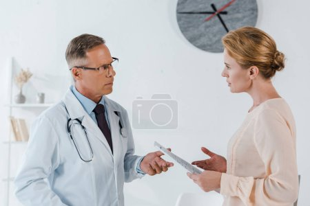Photo for Doctor in glasses gesturing near woman holding clipboard - Royalty Free Image