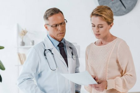 handsome doctor in glasses and woman looking at document