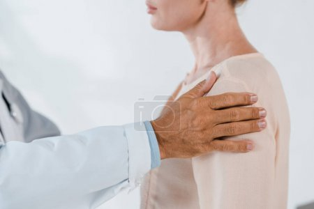 Photo pour Vue recadrée du docteur touchant la femme tout en examinant dans la clinique - image libre de droit