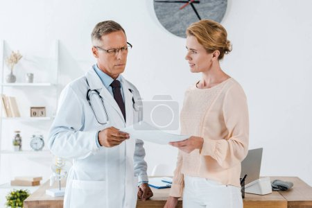 Photo for Doctor in glasses and white coat looking at document near attractive woman - Royalty Free Image