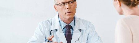 Photo pour Tir panoramique du docteur dans le manteau blanc regardant la femme et faisant des gestes dans la clinique - image libre de droit