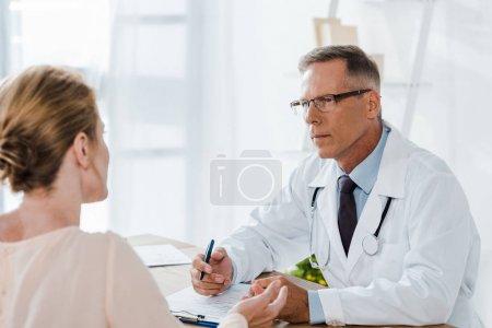 Photo pour Foyer sélectif du docteur dans le manteau blanc regardant la femme et le stylo de fixation dans la clinique - image libre de droit