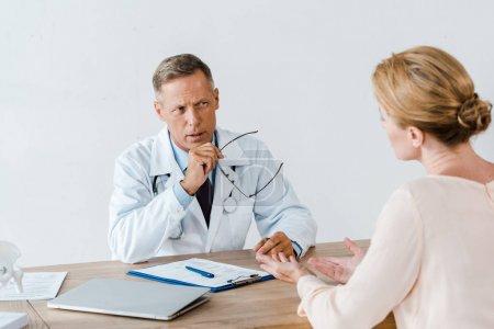 Photo pour Foyer sélectif du médecin en manteau blanc regardant la femme et tenant des lunettes à l'hôpital - image libre de droit