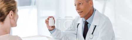 Photo pour Plan panoramique du médecin tenant le flacon et regardant le patient - image libre de droit