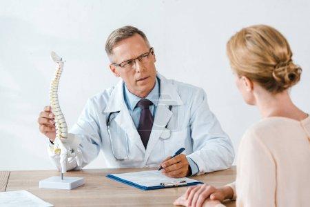 Photo pour Foyer sélectif du docteur dans des glaces touchant le modèle de colonne vertébrale et regardant la femme - image libre de droit