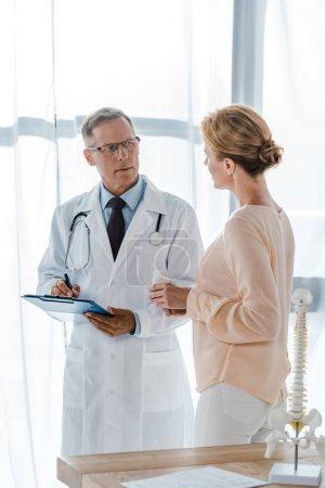 Photo pour Docteur dans des glaces retenant le presse-papiers avec le stylo et regardant la femme avec la bouteille - image libre de droit