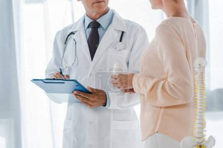 Photo for Cropped view of doctor holding clipboard and pen near woman with bottle - Royalty Free Image