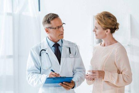 Photo pour Docteur retenant le presse-papiers et le stylo tout en écrivant le diagnostic et regardant la femme avec la bouteille - image libre de droit