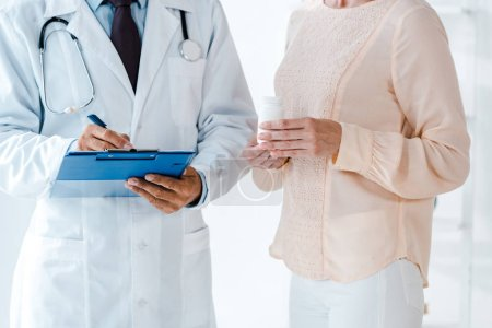 Photo for Cropped view of man holding clipboard and pen while writing diagnosis near woman with bottle - Royalty Free Image