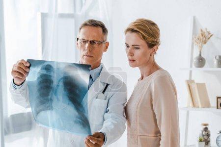 Photo pour Beau médecin et patient attrayant regardant les rayons X dans la clinique - image libre de droit