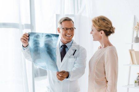 Photo for Happy doctor looking at attractive patient and holding  x-ray in clinic - Royalty Free Image