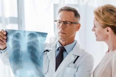 Photo pour Femme heureuse regardant le médecin en manteau blanc tenant des rayons X à la clinique - image libre de droit