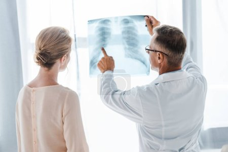 Photo for Doctor in white coat pointing with finger at x-ray near woman in clinic - Royalty Free Image