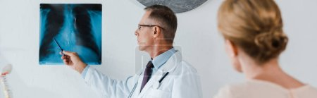 Photo for Panoramic shot of doctor in white coat holding pen near x-ray and woman in clinic - Royalty Free Image