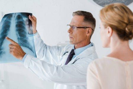 Photo pour Foyer sélectif du médecin sérieux dans les lunettes pointant du doigt à la radiographie près de la femme - image libre de droit