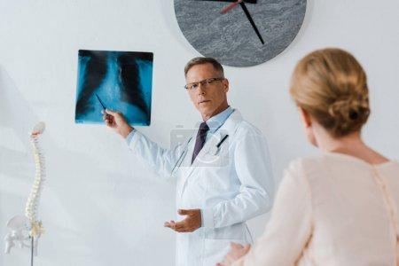 Photo pour Foyer sélectif du docteur dans le manteau blanc et les verres retenant le stylo près de la radiographie et de la femme dans la clinique - image libre de droit
