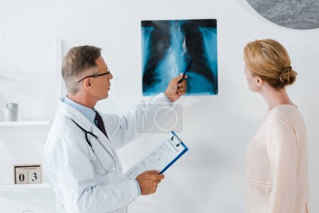 Photo for Doctor in glasses holding pen near x-ray and patient in clinic - Royalty Free Image