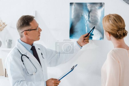 Photo for Doctor in glasses holding pen near x-ray and woman in clinic - Royalty Free Image
