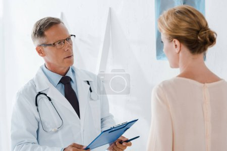 Photo for Doctor in glasses holding pen and clipboard near patient in clinic - Royalty Free Image