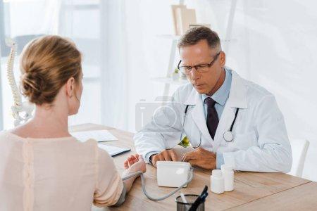 Photo pour Foyer sélectif du médecin dans les lunettes de mesure de la pression artérielle de la femme - image libre de droit