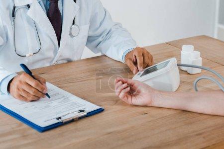 Photo pour Vue recadrée du médecin tenant le stylo près du presse-papiers tout en mesurant la pression artérielle de la femme - image libre de droit