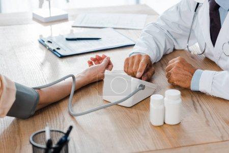 Foto de Vista recortada del médico que mide la presión arterial de la mujer cerca de los biberones - Imagen libre de derechos