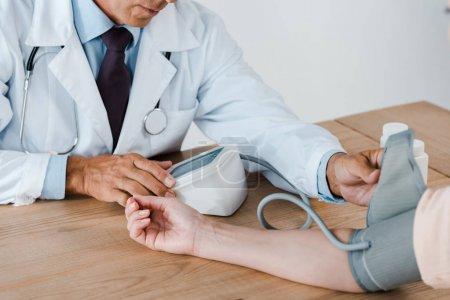Photo pour Vue recadrée du médecin mesurant la pression artérielle du patient en clinique - image libre de droit