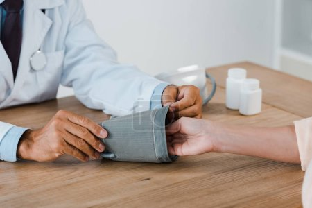 Photo pour Vue recadrée du médecin mesurant la pression artérielle de la femme à l'hôpital - image libre de droit