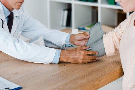 Photo pour Vue recadrée du docteur mesurant la tension artérielle de la femme sur la table à l'hôpital - image libre de droit