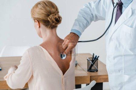 Photo pour Vue recadrée du médecin en manteau blanc examinant la femme à la clinique - image libre de droit