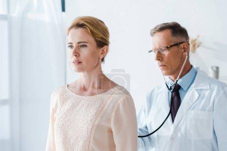 beau médecin dans des lunettes examinant femme attrayante dans la clinique